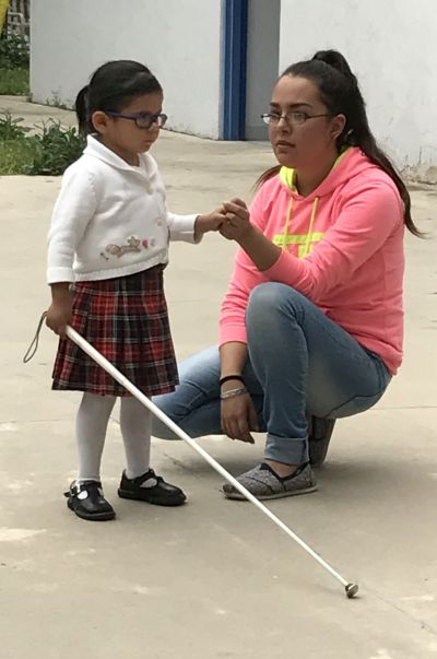 Student learning to use a cane with teacher guiding