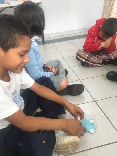 Students playing a braille game on the floor